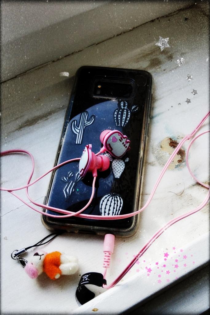 Ein Handy, an das Pusheen-Kopfhörer angeschlossen sind.